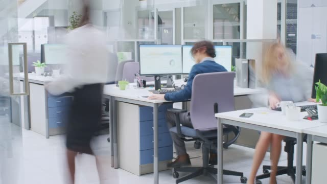 vídeos y material grabado en eventos de stock de time-lapse en la oficina del espacio abierto moderno empresarios y empreseras trabajando, caminando por pasillo, usando tabletas, teniendo discusiones, encontrando soluciones y trabajando en computadoras de escritorio - liado