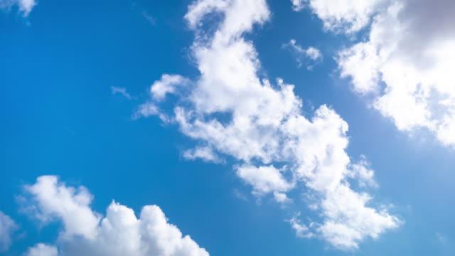 澄んだ青空でふわふわの白い雲を動かすスピードモーションの4kタイムラプス低角画ワイドショット。明るい夏の朝の日に空を移動する時間経過ふわふわ雲。雲景の背景。 - 多重露出点の映像素材/bロール