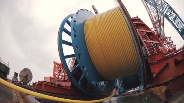 timelapse massive metal wheel roll and unroll long yellow hose, day night change - cartello economico video stock e b–roll