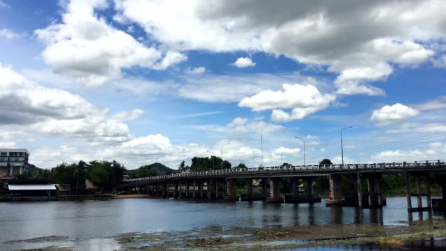 Time-lapse: Morning clouds blue sky with the Bridge River Kwai Time-lapse: Morning clouds blue sky with the Bridge River Kwai and Tourists walking on the bridge over the River Kwai at sunset or sunrise. daylight savings stock videos & royalty-free footage