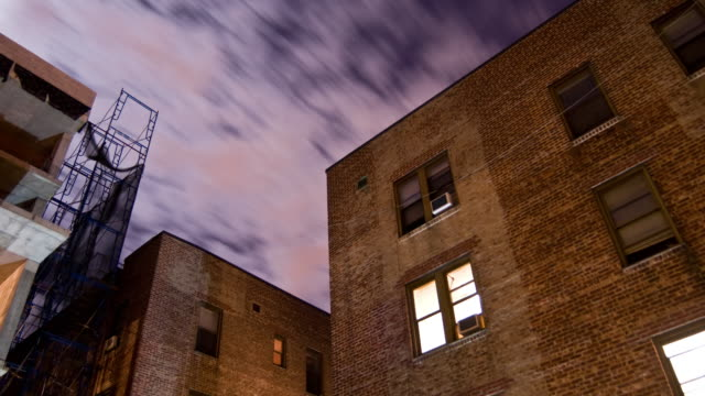 Timelapse - Night Clouds over Apartments A nighttime time lapse of clouds and stars over a typical brick apartment building. brick stock videos & royalty-free footage