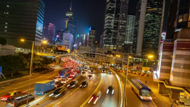 time-lapse: night traffic in central and admiralty hong kong highway with skyline building cityscape in background - центральный район стоковые видео и кадры b-roll