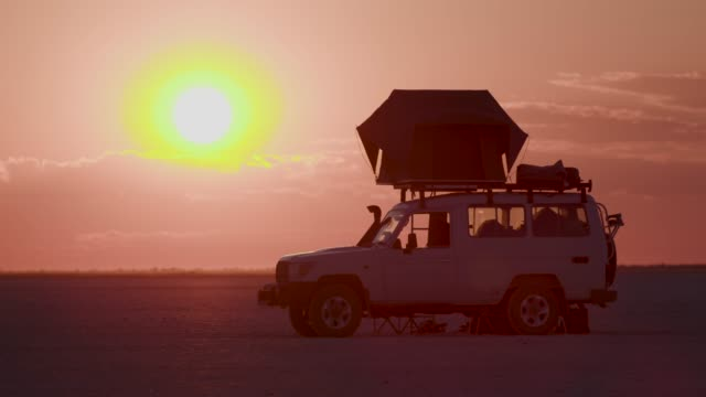 Time-lapse of a 4x4 tourist vehicle and the sun setting in the Makgadikgadi Pans,Botswana Time-lapse of a 4x4 tourist vehicle and the sun setting in the Makgadikgadi Pans,Botswana makgadikgadi pans national park stock videos & royalty-free footage