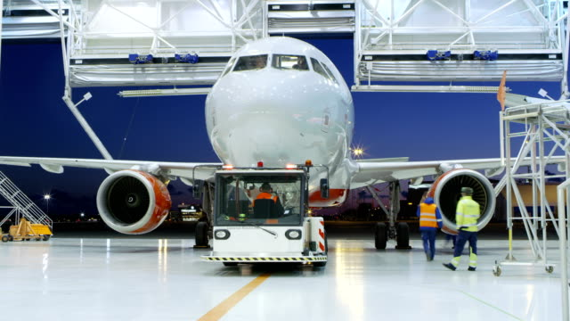 Time-Lapse of a Aircraft Maintenance Hangar Where New Airplane is Toed by a Pushback Tractor/ Tug onto Landing Strip. Crew of Mechanics, Engineers and Drivers Works Busily. video