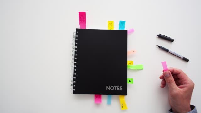 timelapse di un uomo d'affari che mette note adesive in un blocco note - to do list video stock e b–roll
