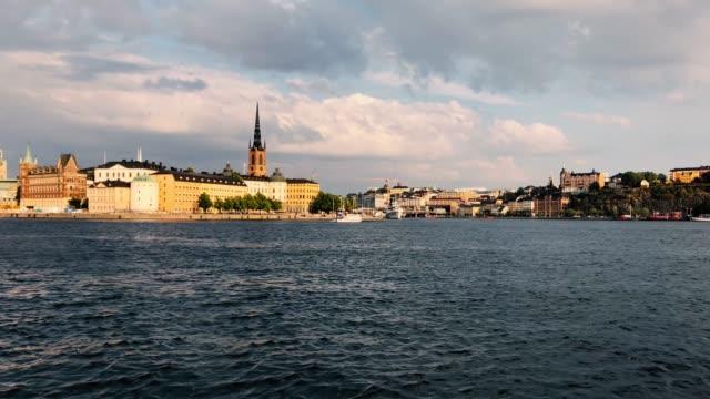 timelapse av en färgstark gamla stan utsikt från stockholms stadshus-djurgården färja passerar i viken och riddarholmskyrkan i bakgrunden - ferry lake sweden bildbanksvideor och videomaterial från bakom kulisserna