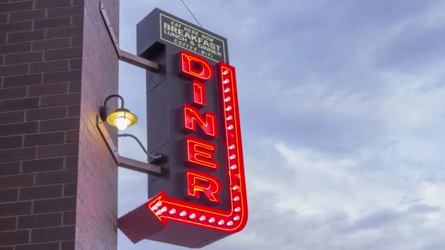 A Timelapse of a Neon Diner Sign and Cloudy Sky