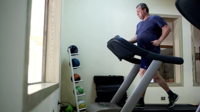 Timelapse of a senior man exercising on treadmill