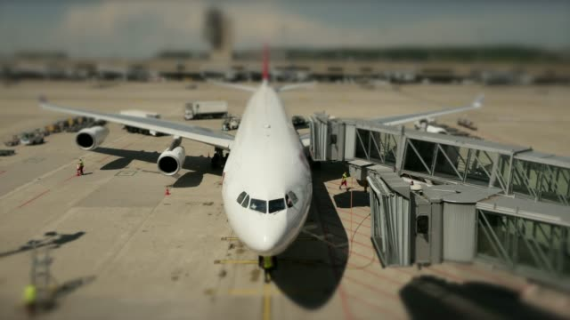 Timelapse of airport vehicles and workers refilling a standing airplane at the airport Aircraft at airport being prepared for flight refueling stock videos & royalty-free footage