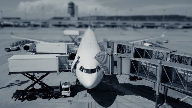 Timelapse of airport vehicles and workers refilling a standing airplane at the airport in black and white video