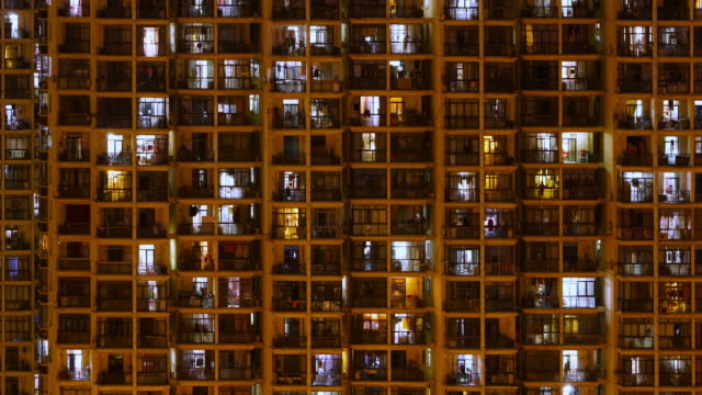 Timelapse of apartment windows at dusk to night. Nighttime time lapse of illuminated building windows at night with people living in flats with balcony in Shanghai, China. facade stock videos & royalty-free footage