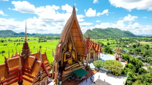 time-lapse of architecture golden big buddha with church and rice field at wat tham sua, tiger cave, kanchanaburi, thailand - tempio video stock e b–roll