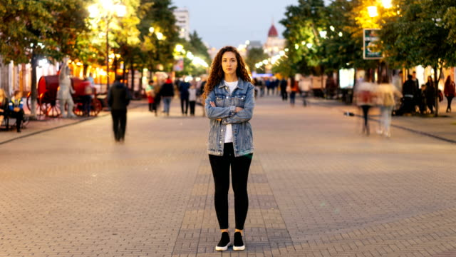 Time-lapse of attractive woman with long curly hair standing in the street with crossed arms and looking at camera on autumn evening when people are moving around. Time-lapse of attractive young woman with long curly hair standing in the street with crossed arms and looking at camera on autumn evening when people are moving around. individuality stock videos & royalty-free footage