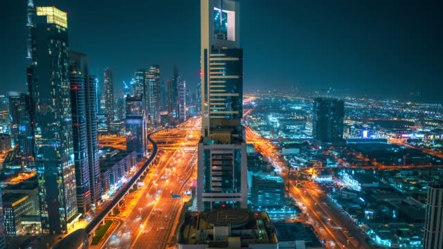 Timelapse of beautiful night Dubai skyline downtown, United Arab Emirates. Aerial view from above of highways with car traffic and skyscrapers buildings video