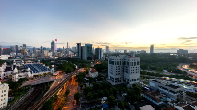 timelapse of beautiful sunrise at Kuala Lumpur city centre from a rooftop of a building, with city skyline, train, and burst sunlight. video