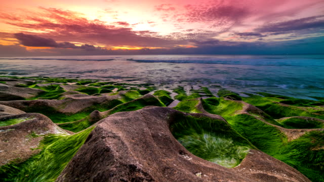 Time-lapse of beautiful sunset on the Balangan beach with frozen volcanic funnels covered with algae on the island of Bali in Indonesia. video