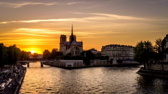 timelapse av båtar i paris vid solnedgången med notre-dame-de-paris kyrka i bakgrunden och personer som vilar på dockorna, visa från tournelle bridge - turistbåt bildbanksvideor och videomaterial från bakom kulisserna