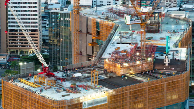 Time-lapse of busy industrial construction site workers with cranes working Time-lapse of busy industrial construction site workers with cranes working civil engineering stock videos & royalty-free footage