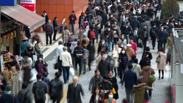 timelapse of busy street of tokyo, japan, showing busy traffic and moving pedestrians - marciapiede video stock e b–roll