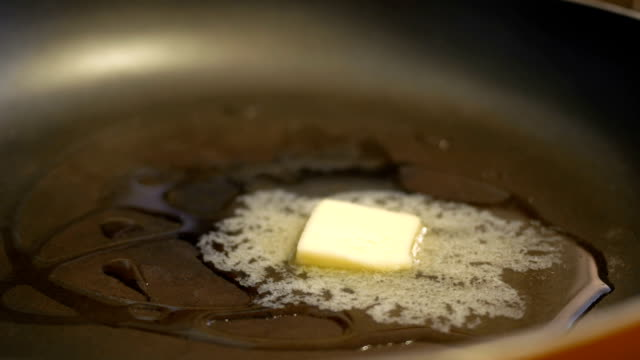 Timelapse of butter melting in a pan on a stove top in restaurant video