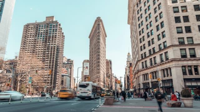 vídeos de stock, filmes e b-roll de 4k uhd lapso de tempo de tráfego de carro e pessoas andando no distrito de construção flatiron, new york city, e.u.a. vida da cidade americana, atração turística de américa, marco do curso, ou conceito do transporte - new york city