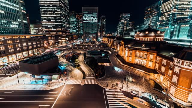 道路を横断する日本人との夜東京駅で交通の 4 k uhd コマ撮り。東京観光、日本の観光、アジアの都市生活、またはアジア輸送の概念 - 多重露出点の映像素材/bロール