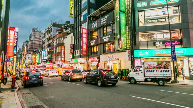 Timelapse of cars and traffic passing through Chengu Road in front of Ximending Shopping district