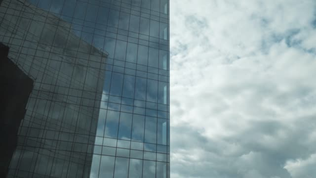 Timelapse of clouds moving and reflecting in glassy skyscraper Timelapse shot of clouds sailing in the sky and reflecting in modern glassy business centre facade stock videos & royalty-free footage