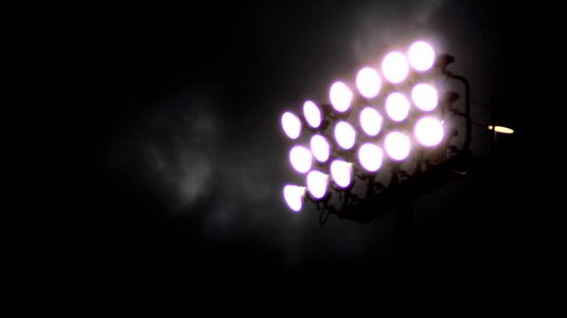 vídeos y material grabado en eventos de stock de timelapse de nubes en movimiento rápido detrás de luces del estadio - deportes de la escuela secundaria