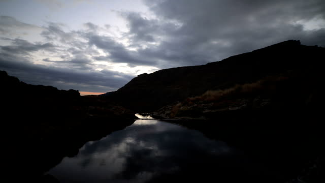 Timelapse of clouds moving over mountain top and stream, dusk to night video