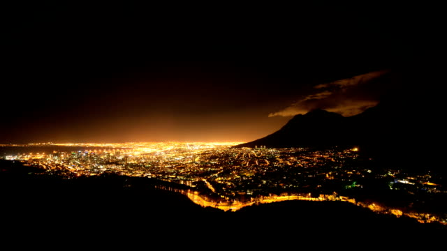 Timelapse of clouds moving over top of Devil's Peak in Cape Town, South Africa. Cape Town city lights video