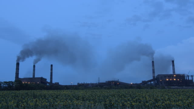 Timelapse of clouds of smoke billowing from smokestacks into the twighlight sky, HD