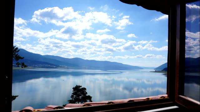 ホリデイ ヴィラの窓から湖の上雲の 4 k タイムラプス - 別荘点の映像素材/bロール
