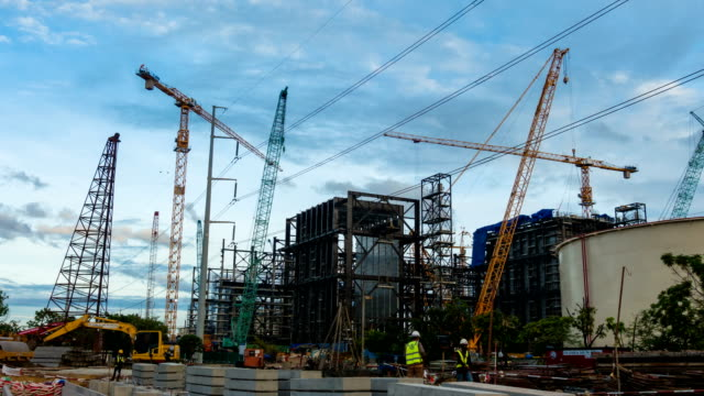 Time-lapse of Combine cycle power plant Construction Site with tower crane, Mobile crane and steel structure of boiler and cooling tower near river