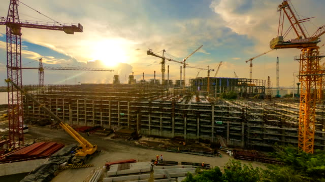 time-lapse of combine cycle power plant construction site with tower crane, mobile crane and steel structure of boiler and cooling tower at dusk 60fps - industria edile video stock e b–roll