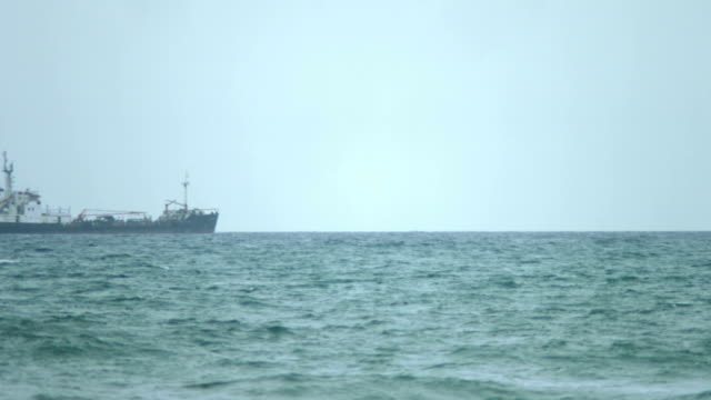 Time-lapse of commercial watercraft crossing stormy ocean waters, carrying goods