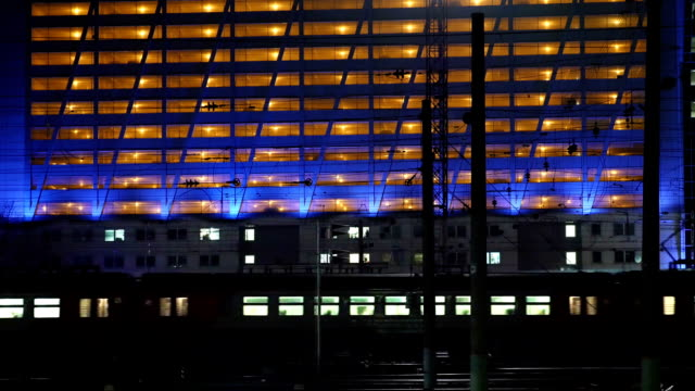 Timelapse of commuter train in the city at night Timelapse of electric train passing by the lighted building in the city at night intercity stock videos & royalty-free footage