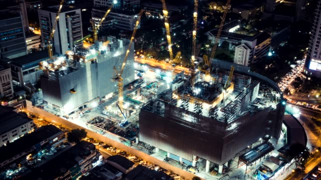 Time-lapse of construction site at night with light trails of traffic in the city, top view. Advanced building technology, busy metro downtown cityscape, or developing industrial country concept