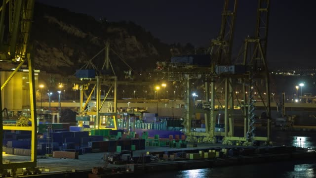 Timelapse of container traffic in industrial port at night, Spain
