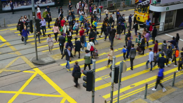 (zoom out) time-lapse of crowd crossing road at zebra crossing in hong kong. - центральный район стоковые видео и кадры b-roll