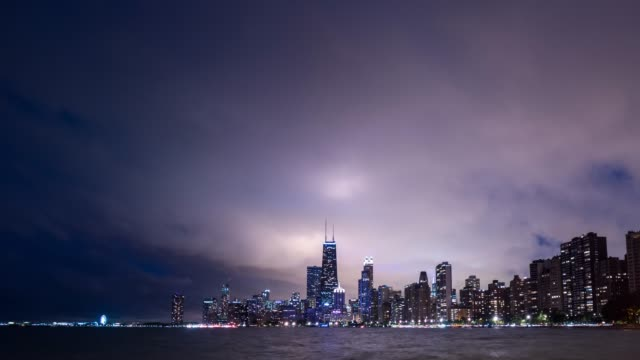 Timelapse of dramatic cumulus clouds move in over the city of Chicago and the water of Lake Michigan at night with city lights on buildings and helicopter passing by.