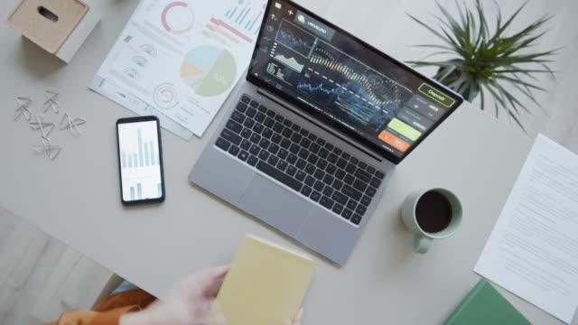 vídeos y material grabado en eventos de stock de timelapse de analista femenina que trabaja en desk en portátil y con diagramas - liado