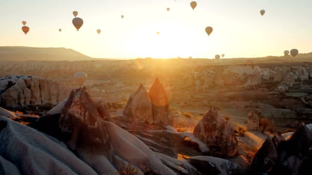 Timelapse of flying air balloons over Cappadocia landscape at sunrise Colorful hot air balloons flying over beautiful Goreme village landscape at sunrise. Cappadocia is famous travel destination with beautiful limestone mountains, Turkey turkey stock videos & royalty-free footage