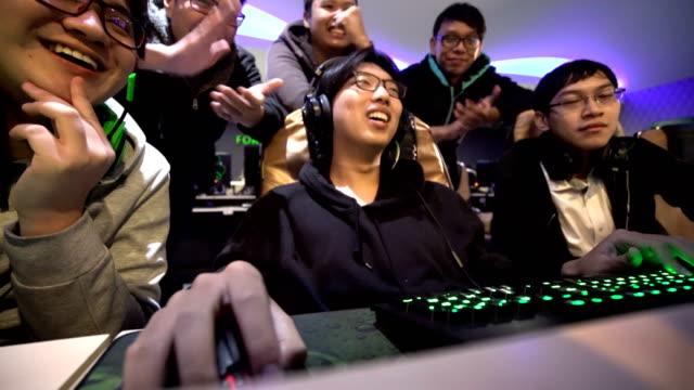 stockvideo's en b-roll-footage met timelapse van gamer vrienden afspelen van video game in internetcafé - kampioenschap