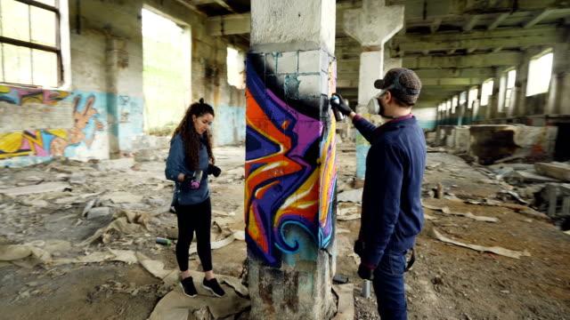 time-lapse av graffiti konstnärer är använda aerosol färg för att dekorera övergav industribyggnad med modern graffiti bilder. kreativitet, gatukonst och människor koncept. - väggmålning bildbanksvideor och videomaterial från bakom kulisserna