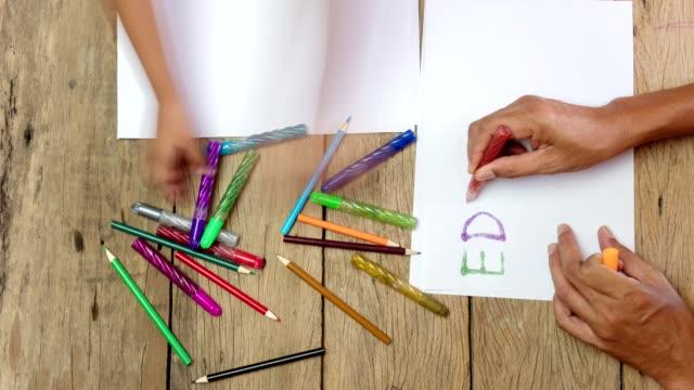 vidéos et rushes de timelapse du père de la main et bébé dessiner du texte de l'éducation sur fond bois animation en stop motion - fournitures scolaires