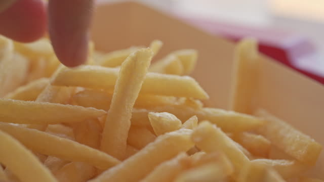 Timelapse of Hand picking French Fries Timelapse of Hand picking French Fries french fries stock videos & royalty-free footage