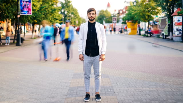 time-lapse of handsome young man in stylish clothing standing in the street of big city and looking at camera with people moving around. urban lifestyle and society concept. - stare in piedi video stock e b–roll