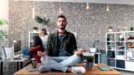 istock Time-lapse of handsome young man relaxing in lotus position on desk in office 1150438410