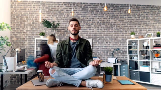 Time-lapse of handsome young man relaxing in lotus position on desk in office Time-lapse of handsome young man hipster relaxing in lotus position on desk in office while colleagues are moving around. Stress management and job concept. zen like stock videos & royalty-free footage